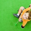 Young boy plays mini golf on putt putt course. — Stock Photo