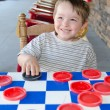 Smiling young boy playing checkers while sitting on rocking chair on porch — Stock Photo