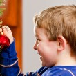 Stock Photo: Young boy decorates Christmas Tree for holiday.