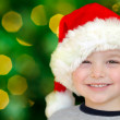 Portrait of young boy in Santa hat in front of Christmas tree — Stock Photo
