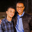 Portrait of African-American father and teenage son outdoors at park — Stock Photo