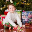 Photo: Young boy unwrapping presents on Christmas morning
