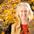 Fall portrait of happy middle-aged blonde woman — Stock Photo #9677698