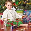 Young boy unwrapping presents on Christmas morning — Stock Photo