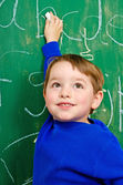 Portrait of young boy after writing on chalkboard for school homework — Stock Photo