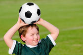 Young boy playing soccer in organized league game — Stock Photo