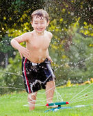 Young boy or kid cools off by playing in water sprinkler at home in his back yard on hot summer day — Stock Photo