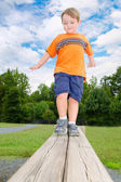 Young boy or kid balancing on beam obstacle on exercise trail outdoors at park — Stock Photo