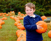 Happy young boy picking a pumpkin for Halloween — Foto de Stock