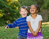 Young African-American girl and young white boy playing together in park — Stock Photo