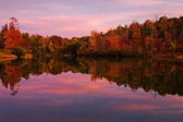 Forest lake surrounded by trees with fall color at dusk. — Stock Photo
