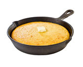 Corn bread in iron skillet isolated on white — Stock Photo