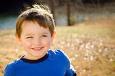 Portrait of happy young boy outdoors in image with copy space — Stock Photo