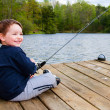 Boy fishing from dock on lake. — Stock Photo #9905771