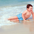 Young boy playing in surf at beach — Stock Photo