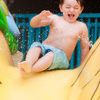 Young boy speeds down water slide — Stock Photo