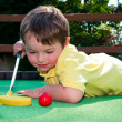 Stock Photo: Young boy plays mini golf on putt putt course.