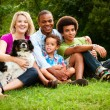 Portrait of mixed race family at park - Stock Photo