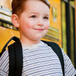 Boy in front of school bus — Stock Photo