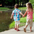 Hispanic girl and boy walk around pond. — Stock Photo