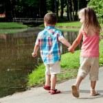Hispanic girl and boy walk around pond. — Stock Photo
