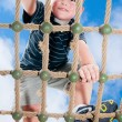 Young boy climbing rope obstacle on kid playground — Stock Photo