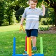 Stock Photo: Young boy or kid playing ring toss outdoors at park during summer.
