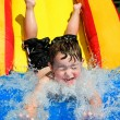 Young boy or kid has fun splashing into pool after going down water slide during summer - Stockfoto