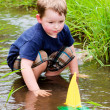 Boy has fun by playing with toy boats in creek at park during spring or summer — Stock Photo