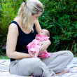 Portrait of happy mother and mixed race newborn baby girl outdoors at park — Stock Photo