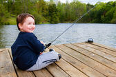 Boy fishing from dock on lake. — Stock Photo
