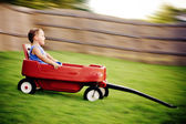 Young boy zooms downhill in wagon in image with motion blur. — Stock Photo