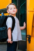 Boy in front of school bus — Stock Photo