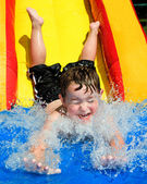 Young boy or kid has fun splashing into pool after going down water slide during summer — Stockfoto
