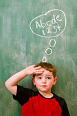 Education school concept of preschooler boy thinking about writing and math in front of chalkboard — Stock Photo