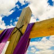 Stock Photo: Cross with purple drape or sash for Easter with blue sky and clouds in background
