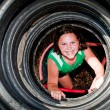 Girl plays in recycled tire tunnel at playground. — Stock Photo #9937183