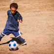 Young African American boy playing soccer — Foto Stock