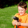 Child plays with water hose outdoors during summer or spring to cool off in hot weather — Stock Photo #9981270