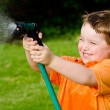 Child plays with water hose outdoors during summer or spring to cool off in hot weather — Stock Photo #9981271
