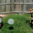 Two kids playing ball in a backyard — Stock Photo
