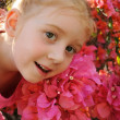 Young girl in front of pink flowers — Stock Photo