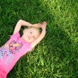Young girl in pink lying on green grass — Stock Photo
