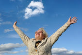 Happy senior lady with hands out stretched against blue sky — Stock Photo