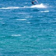 Lone windsurfer in the ocean catching a wave — Stock Photo