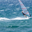 Lone windsurfer in the ocean catching a wave - Stock Photo