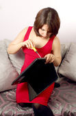 Attractive young women sitting on sofa with laptop and screwdriver — Stock Photo