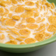Foto Stock: Cornflakes and milk in green plate close up