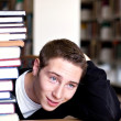 Overwhelmed Student with Piled Books - Stock Photo