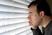 Man Peeking Through Blinds — Stock Photo